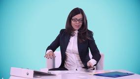 Den lyckliga le unga brunetten i en affärsdräkt visar tummen på kameran Hon sitter i kontoret bak ett skrivbord lager videofilmer