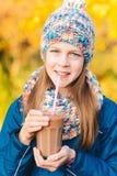 Den lyckliga le unga flickan som dricker choklad, mjölkar Arkivbilder