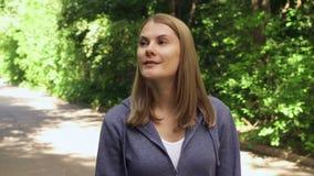Den lyckliga le unga kvinnan i hoodies som omkring går i soligt, parkerar på dag för sommar` s stock video