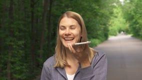 Den lyckliga le unga kvinnan i hoodies som omkring går i soligt, parkerar på dag för sommar` s och samtal på telefonen stock video