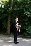 Den lyckliga leendebrudgummen väntar på bruden med den fantastiska buketten av blommor i klassisk dräkt med flugan i gräsplan fotografering för bildbyråer