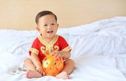 Den lyckliga lilla asiatet behandla som ett barn pojken i traditionell kinesisk klänning med en spargris som hemma sitter på säng fotografering för bildbyråer
