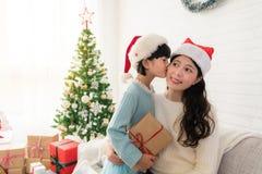 Den lyckliga lilla asiatiska flickan ger hennes moder en kyss arkivfoto