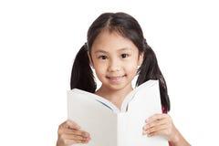 Den lyckliga lilla asiatiska flickan läste en bok Arkivfoto