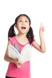 Den lyckliga lilla asiatiska flickan läste en bok och pekar upp Arkivbilder