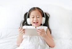 Den lyckliga lilla asiatiska flickan som använder hörlurar, lyssnar musik av smartphonen som ler, medan ligga på säng hemma arkivbild