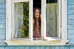 Den lyckliga lilla flickan öppnar ett fönster av det lantliga huset i den tidiga soliga morgonen Arkivfoton