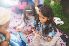 Den lyckliga lilla flickan firar hennes födelsedag med kakan utanför royaltyfri fotografi