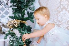 Den lyckliga lilla flickan i den vita klänningen dekorerar trädet i det jul dekorerade rummet Royaltyfria Foton