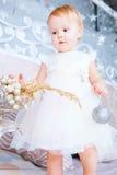 Den lyckliga lilla flickan i den vita klänningen dekorerar trädet i det jul dekorerade rummet Arkivfoto