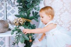 Den lyckliga lilla flickan i den vita klänningen dekorerar trädet i det jul dekorerade rummet Royaltyfria Bilder