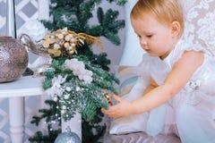 Den lyckliga lilla flickan i den vita klänningen dekorerar trädet i det jul dekorerade rummet Fotografering för Bildbyråer