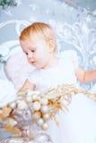 Den lyckliga lilla flickan i den vita klänningen dekorerar trädet i det jul dekorerade rummet Arkivfoton