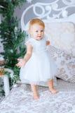 Den lyckliga lilla flickan i det vita klänninganseendet i den dekorerade julen hyr rum Royaltyfri Foto