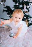 Den lyckliga lilla flickan i det vita klänninganseendet i den dekorerade julen hyr rum Royaltyfri Bild