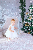 Den lyckliga lilla flickan i det vita klänninganseendet i den dekorerade julen hyr rum Royaltyfri Fotografi