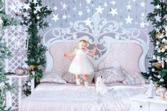 Den lyckliga lilla flickan i det vita klänninganseendet i den dekorerade julen hyr rum Royaltyfria Bilder