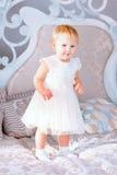 Den lyckliga lilla flickan i det vita klänninganseendet i den dekorerade julen hyr rum Arkivbild