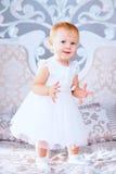 Den lyckliga lilla flickan i det vita klänninganseendet i den dekorerade julen hyr rum Royaltyfria Foton