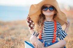 Den lyckliga lilla flickan i en stor hatt Arkivbild