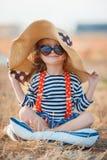 Den lyckliga lilla flickan i en stor hatt Royaltyfri Bild