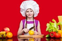 Den lyckliga lilla flickan i enhetliga snitt för kock bär frukt i kök Fotografering för Bildbyråer