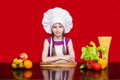 Den lyckliga lilla flickan i enhetliga snitt för kock bär frukt i kök Arkivfoto
