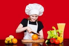 Den lyckliga lilla flickan i enhetliga snitt för kock bär frukt i kök Royaltyfria Foton