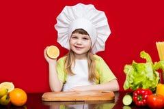 Den lyckliga lilla flickan i enhetliga snitt för kock bär frukt i kök Royaltyfri Fotografi