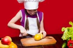 Den lyckliga lilla flickan i enhetliga snitt för kock bär frukt i kök Arkivfoton