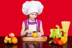 Den lyckliga lilla flickan i enhetliga snitt för kock bär frukt i kök Royaltyfri Foto