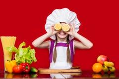 Den lyckliga lilla flickan i enhetliga snitt för kock bär frukt i kök Royaltyfri Bild