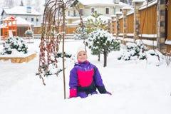 Den lyckliga lilla flickan i färgrik dräkt- och vithatt spelar med snö Arkivbild