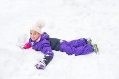 Den lyckliga lilla flickan i färgrik dräkt- och vithatt spelar med snö Royaltyfria Bilder