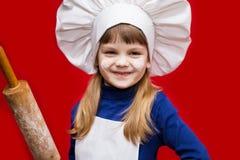 Den lyckliga lilla flickan i kocklikformig rymmer kavlen isolerad på rött Ungekock Ingredienser och kök bearbetar på vitbakgrund royaltyfria bilder