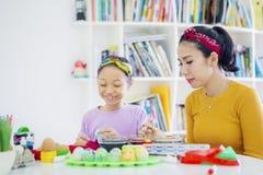 Den lyckliga lilla flickan målar ägg med hennes moder royaltyfri bild