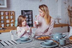Den lyckliga lilla flickan och hennes härliga unga moder har frukosten tillsammans i ett vitt kök De dricker mjölkar och äter kak arkivbild