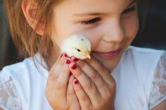 Den lyckliga lilla flickan rymmer en höna i hans händer Barn med poul royaltyfria foton