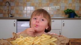 Den lyckliga lilla flickan som äter en fransman, steker på köket lager videofilmer
