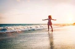 Den lyckliga lilla flickan som kör inom vatten som fördelar hennes händer upp på stranden - behandla som ett barn ha gyckel som g royaltyfria bilder