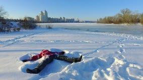 Den lyckliga lilla flickan som ligger på insnöad stad, parkerar Spela för snö lycklig ferievinter stock video