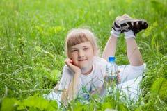 Den lyckliga lilla flickan som vilar i sommaren, parkerar royaltyfria bilder