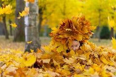 Den lyckliga lilla flickan spelar med höstsidor i parkera fotografering för bildbyråer