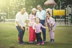 Den lyckliga lilla flickan spelar med hennes familj i parkerar royaltyfri bild