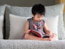 Den lyckliga lilla gulliga flickan läser boken på den vita soffan Ed royaltyfria bilder