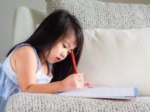 Den lyckliga lilla gulliga flickan skriver boken med den röda blyertspennan på th royaltyfria foton
