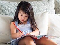 Den lyckliga lilla gulliga flickan skriver boken med den röda blyertspennan på th arkivfoton