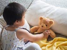 Den lyckliga lilla gulliga flickan spelar doktorn med stetoskopet och är fotografering för bildbyråer
