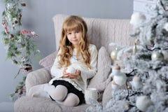 Den lyckliga lilla le flickan med kastar snöboll nära julgranen royaltyfri bild