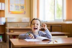 Den lyckliga lilla le flickan som sitter p? skrivbordet i grupprum och, b?rjar f?rsiktigt att dra i en ren anteckningsbok lycklig fotografering för bildbyråer